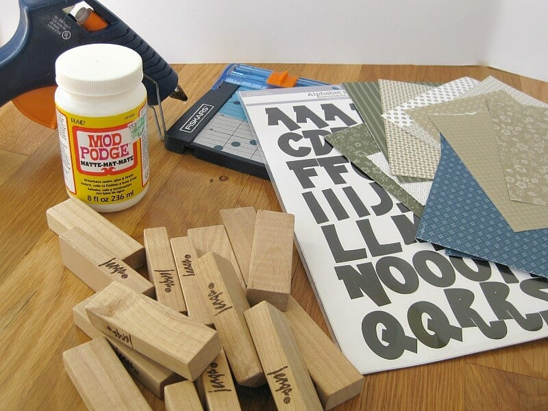 supplies scattered on table, wood blocks, decorative paper, letter stickers, Mod Podge, glue gun and paper cutter