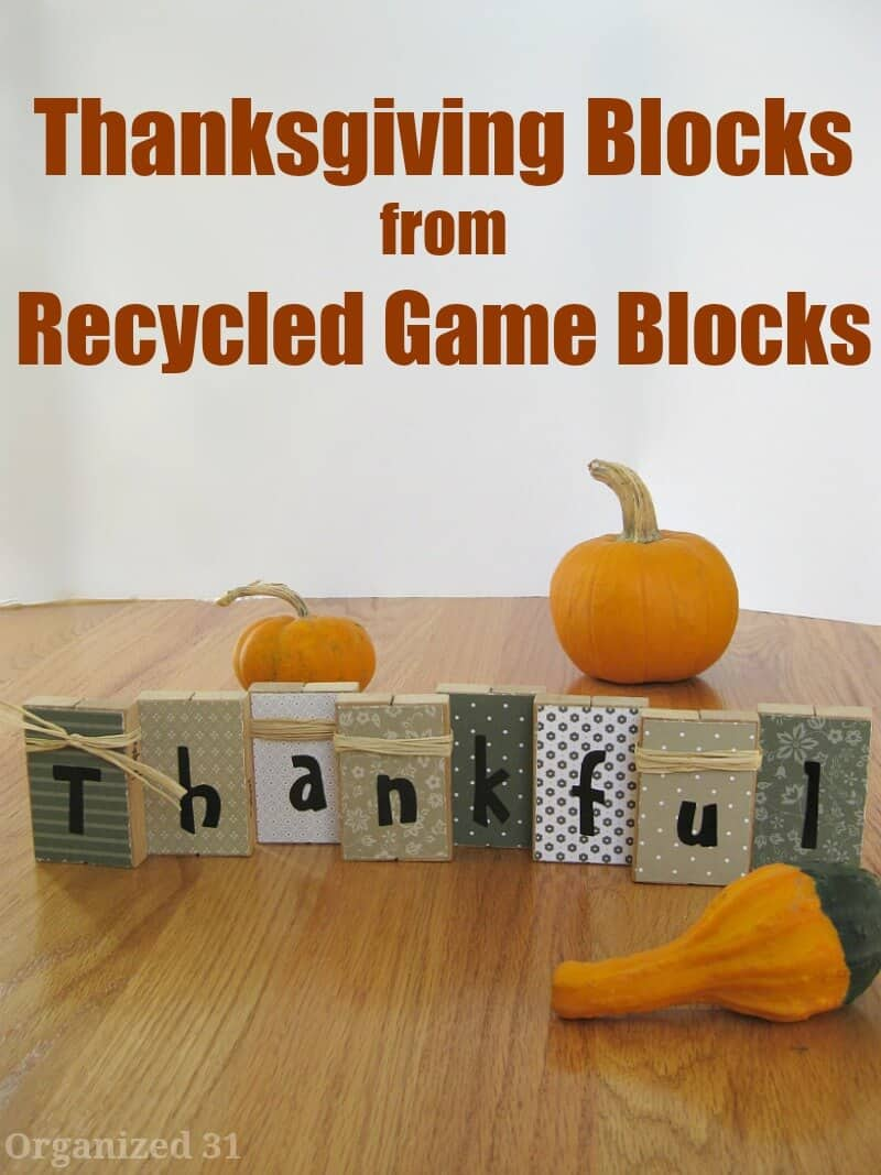 """rustic looking blocks spelling out """"thankful"""" with small pumpkins and gourds on table"""