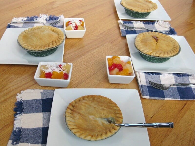 table set with plates, blue and white napkins, forks and pot pies