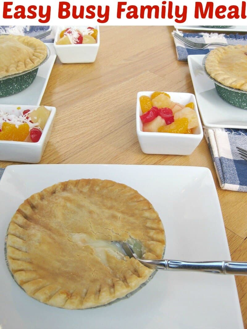 pot pie with fork on white plate on table set with other plates with pot pies