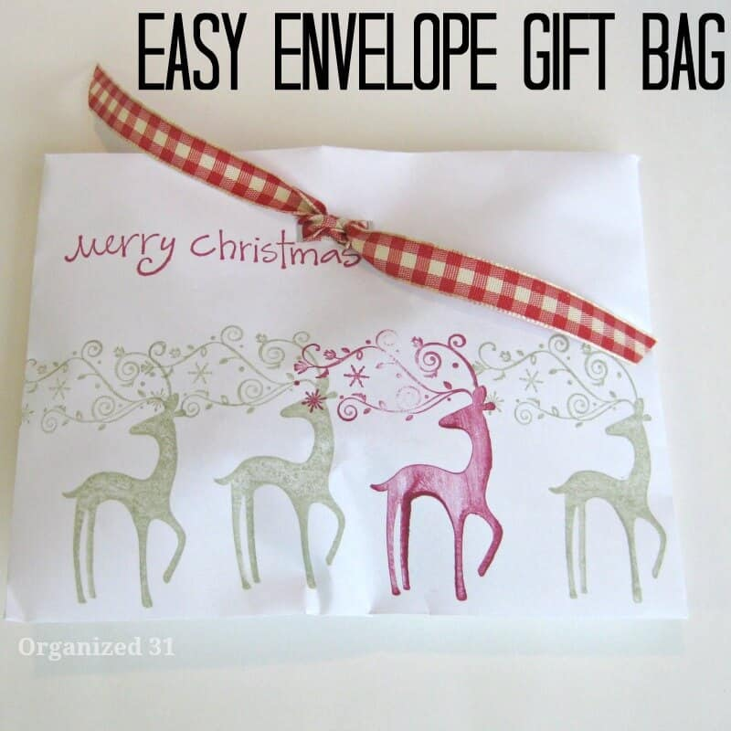 white envelope with red checkered bow and green and red reindeer  on the envelope
