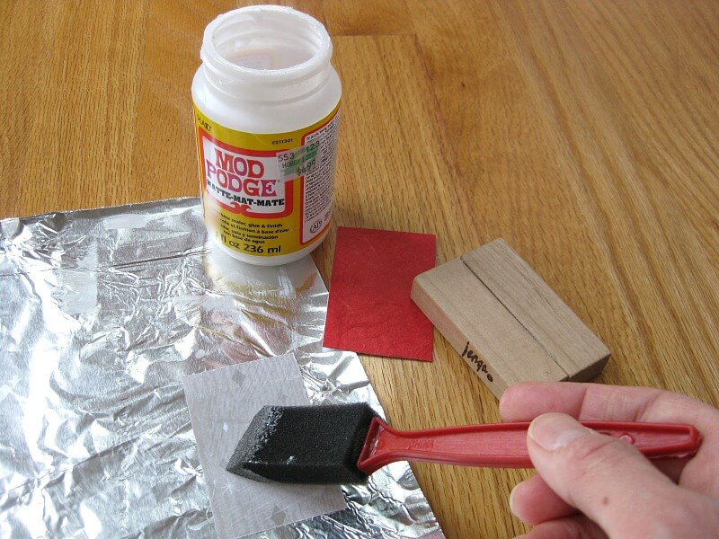 hand holding brush adding glue to paper next to wood block and bottle of decoupage glue