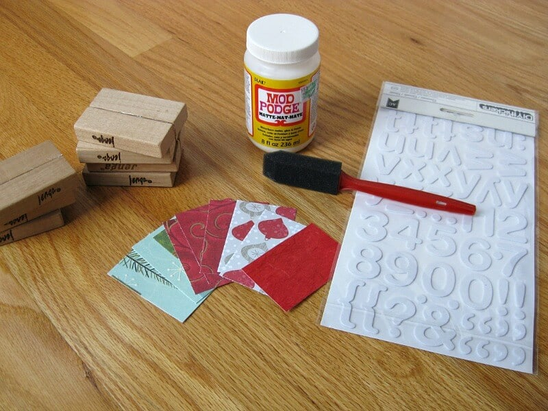 stack of wood block, bottle Mod Podge, brush, small squares of Christmas decorative paper and sheet of white letter stickers