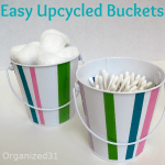 white buckets with colorful stripes holding cotton balls and swabs