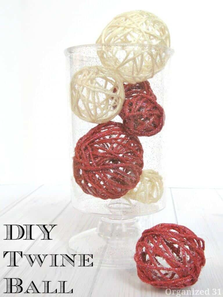 Red and white twine balls in a vase on a white wood table