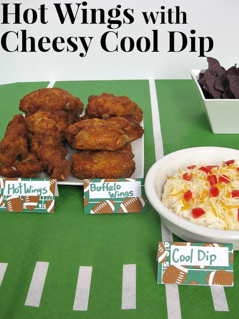 plate of hot wings, bowl of tortilla chips and bowl of cheese tip on green tablecloth that looks like football field