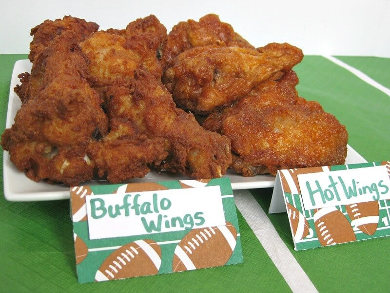close up plate of wings with football descriptive signs in front