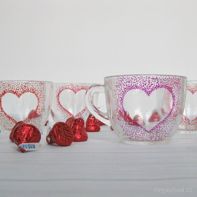 3 clear cups with red and pink dot hearts and red candy on table