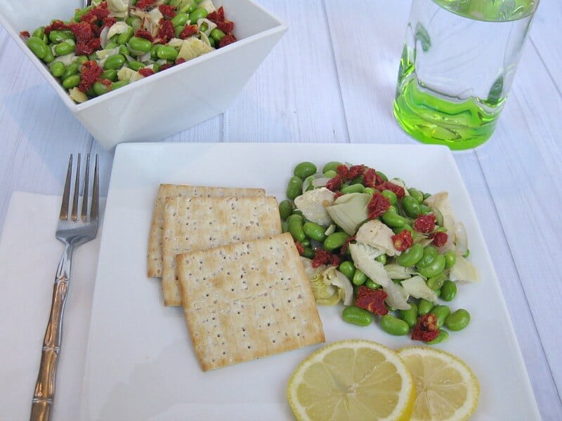 overhead view of plate of salad, crackers and lemon slices with glass of water on white wood table