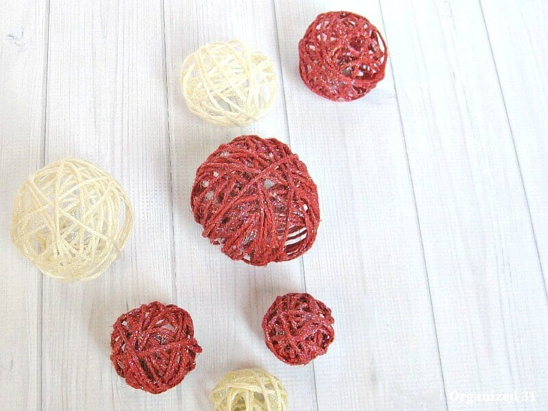 red and white twine balls on white wood table