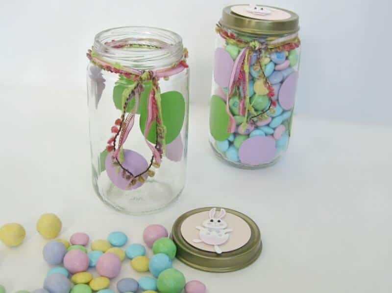 2 decorated upcyled glass jars with pastel candy in one and scattered on white table