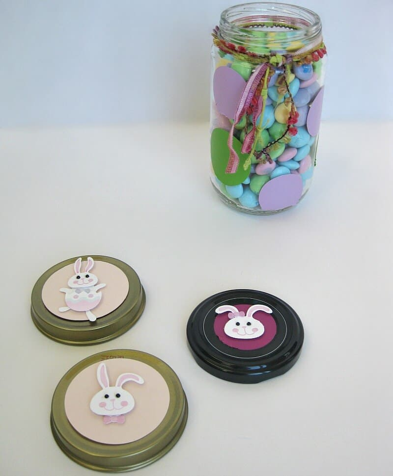 Decorated glass jar filled with pastel candy with 3 jar lids decorated with smiling rabbit faces