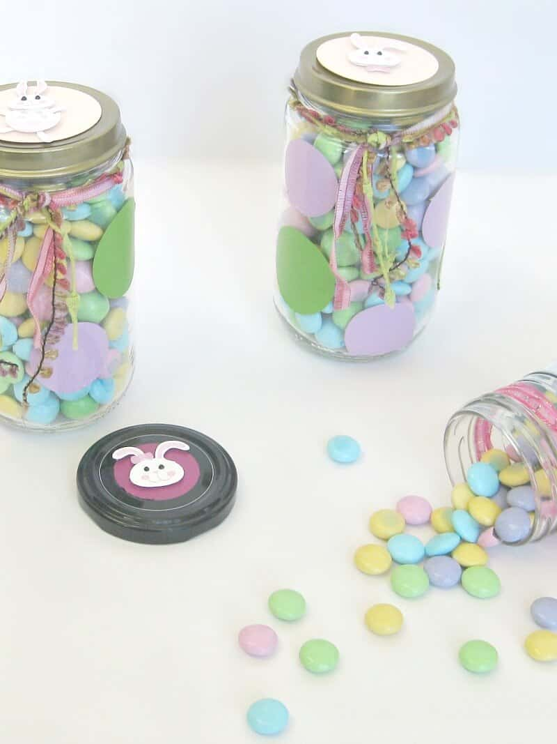 3 decorated recycled glass jars filled with pastel candy and decorated with smiling Easter bunny faces