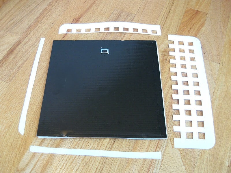 black square with pieces of white plastic grid cut to fit on wood table