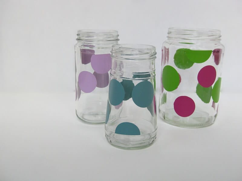3 recycled glass jars decorated with colorful dots