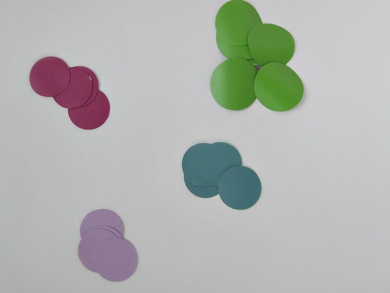 piles of 4 different colors of circle stickers on white table