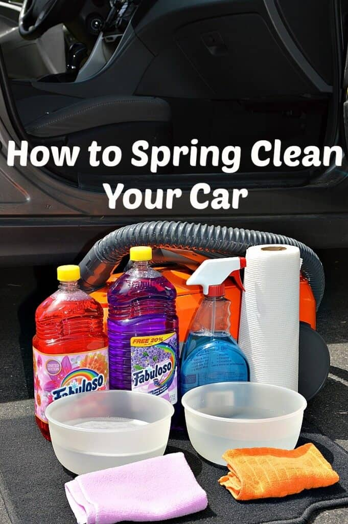 orange vacuum with cleaning supplies sitting in front of open car door with white text overlay reading How to Spring Clean Your Car