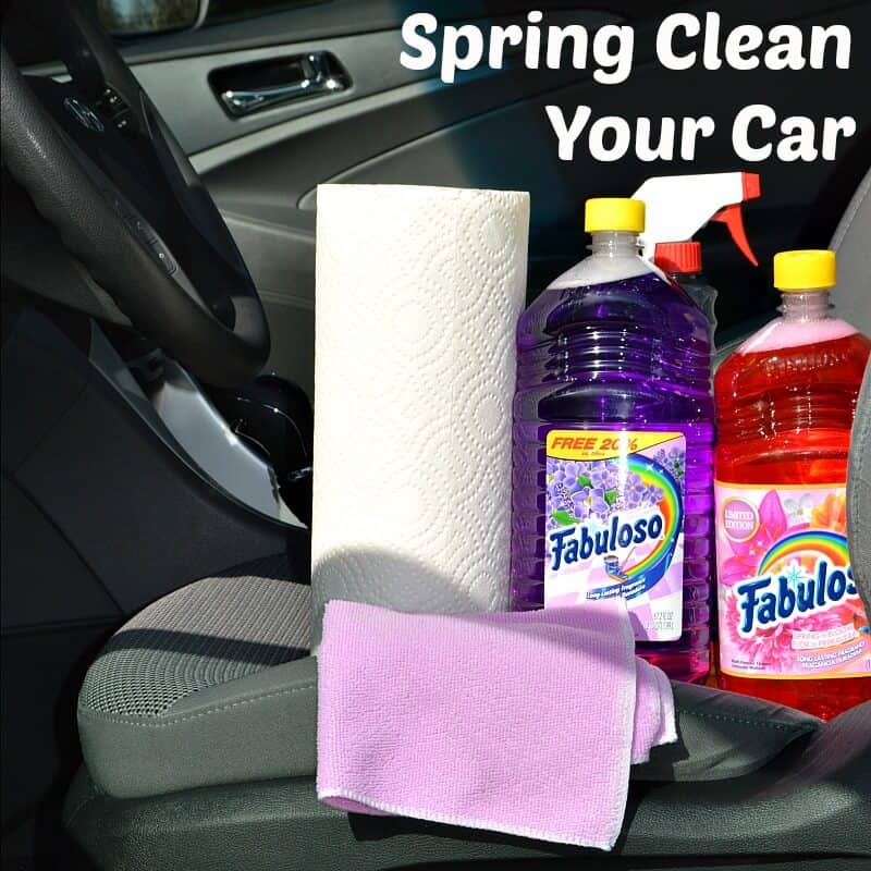 roll of paper towels cleaning cloth and bottles of cleaning supplies sitting on car seat with title text reading Spring Clean Your Car