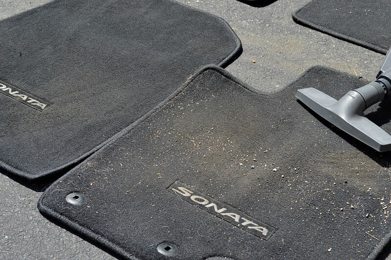 clean car floor mat next to dirty car floor mat with vacuum head