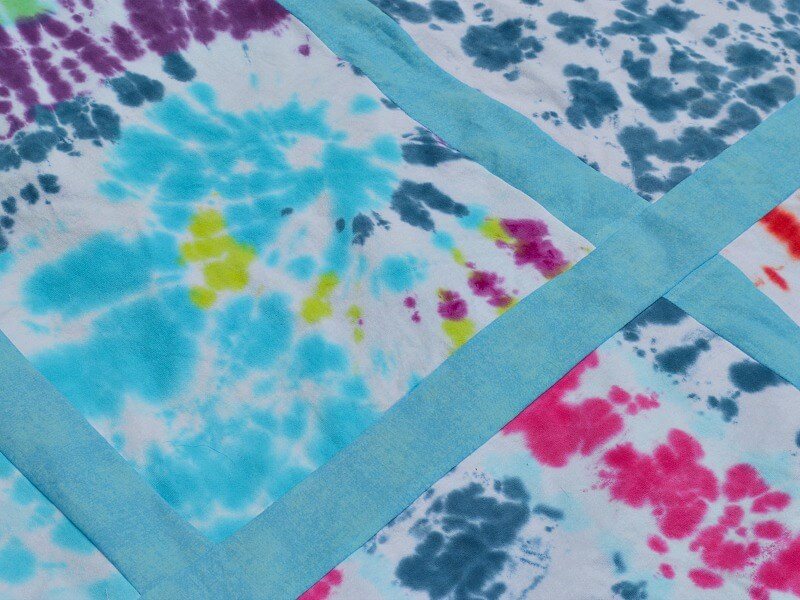 close up of sashing and square of tie-dyed quilt