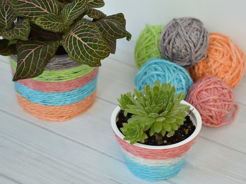 2 plant pots wrapped with colorful yarn and stack of colorful yarn balls