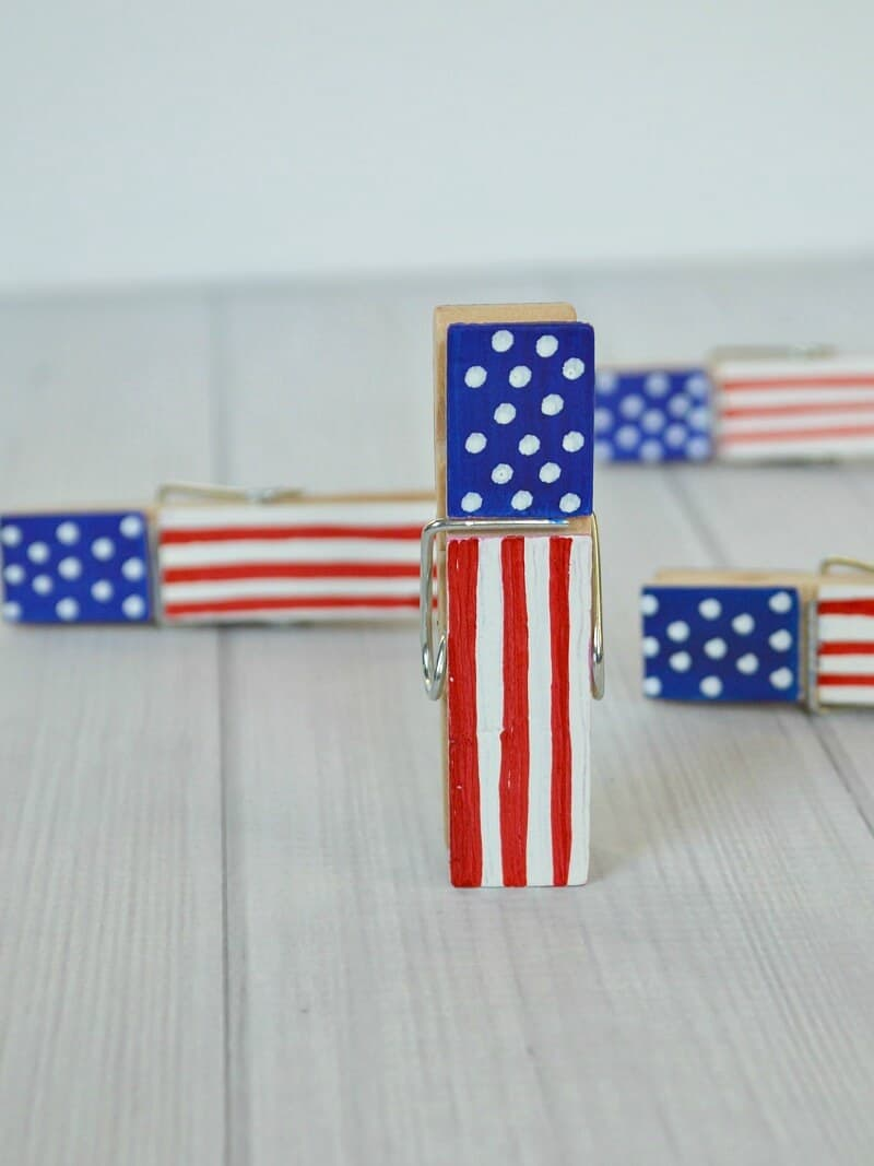close up of flag painted wood clothes pin on white wood table