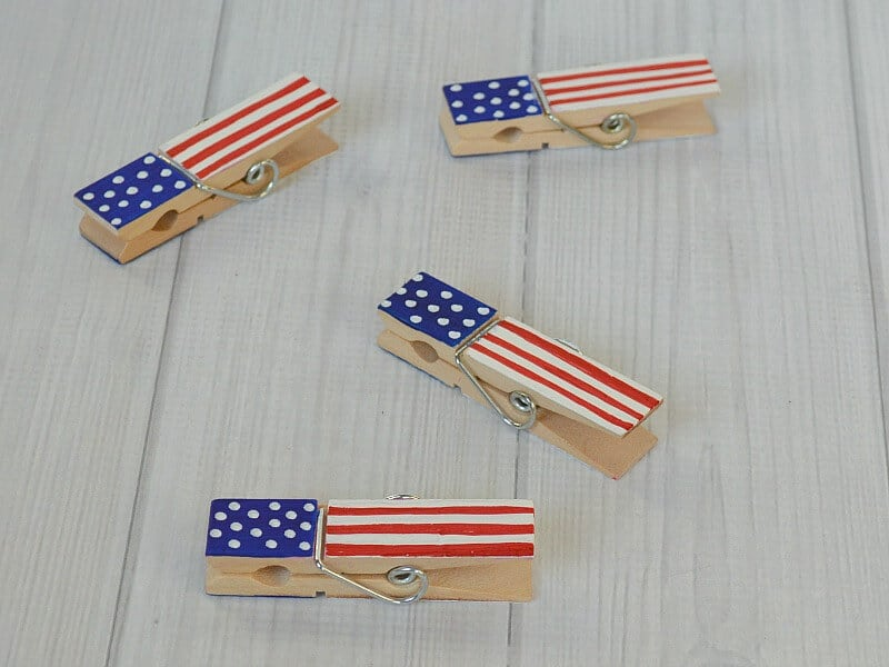 close up of completed DIY flag painted clothes pins on white wood table