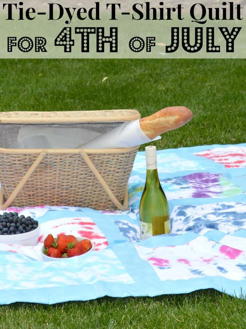 picnic basket with loaf of bread, bottle of wine and 2 bowls of fruit of colorful tie-dyed blanket on grass