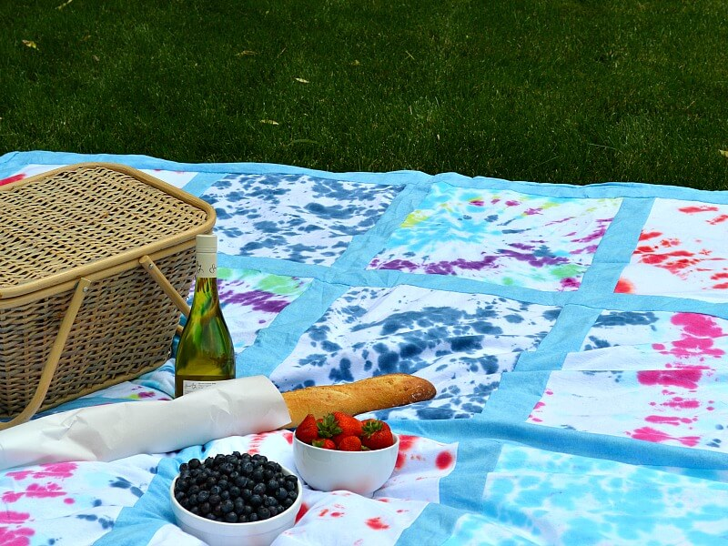 close up of picnic basket with loaf of bread, bottle of wine and 2 bowls of fruit of colorful tie-dyed blanket on grass