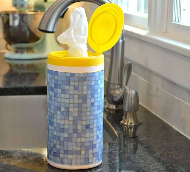 Disinfecting wipes container decorated with blue paper by kitchen sink