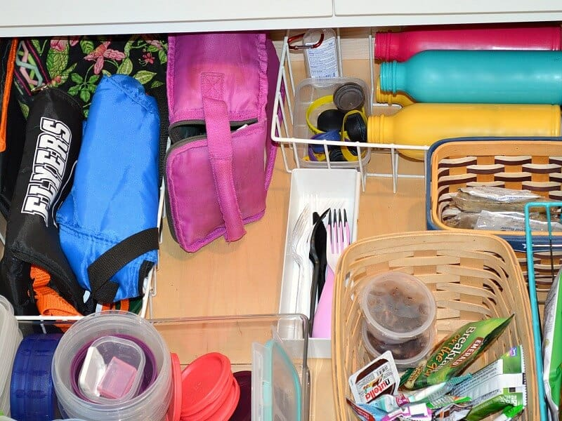 overhead view of organized kitchen drawer with school lunch box supplies