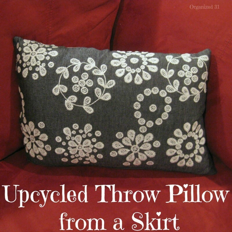 dark grey pillow with white flowers on red chair