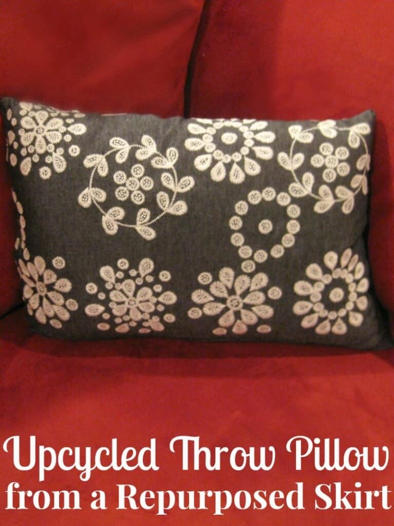 grey pillow with white flowers on red chair