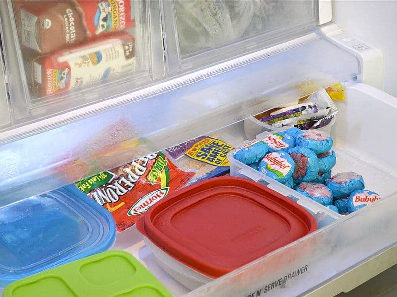 Organized drawer in refrigerator with cheese, lunch meat and storage containers.