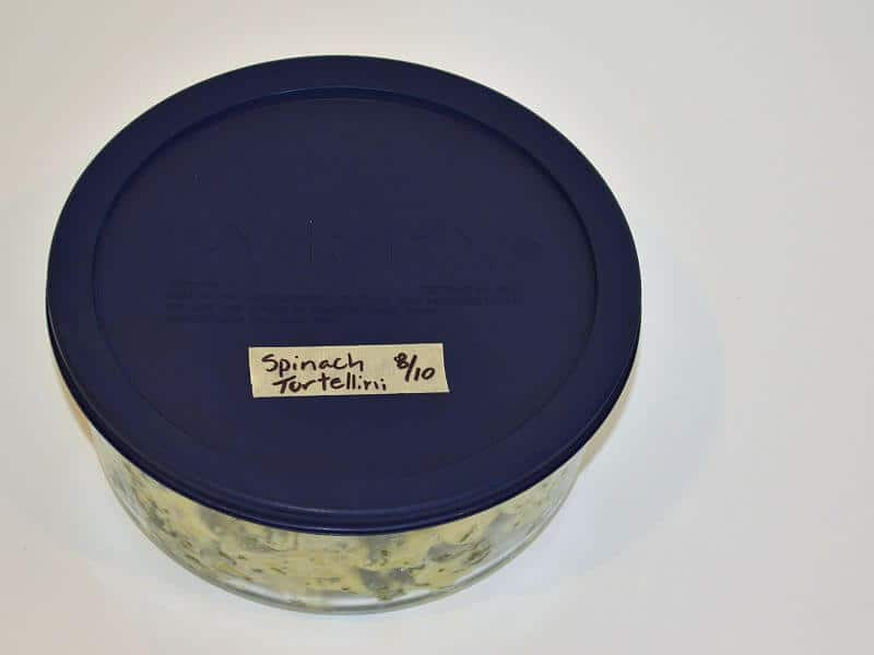 glass container with blue lid labeled with date and contents