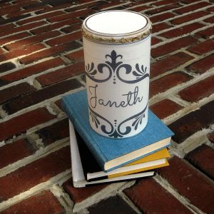 decorated tin on top of stack of books on brick