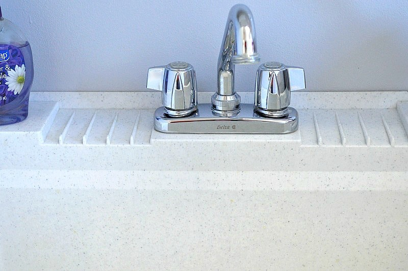 shiny faucet on clean white plastic utility sink