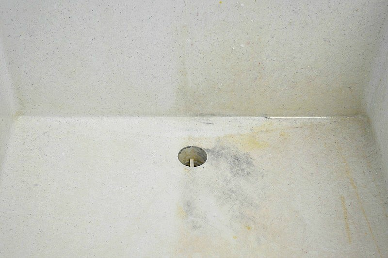 white utility sink with one side stained and one side clean