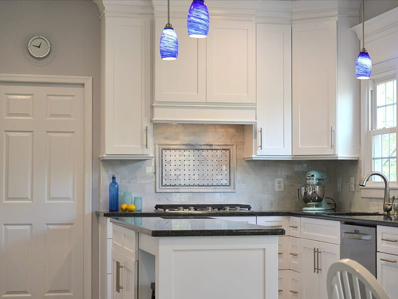neatly organized white and black kitchen with blue pendant lights