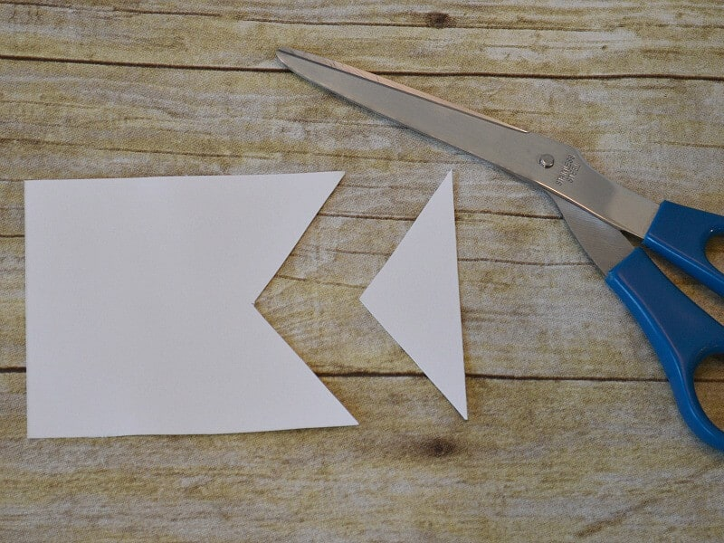 triangle cut out of white square and scissors on wood table
