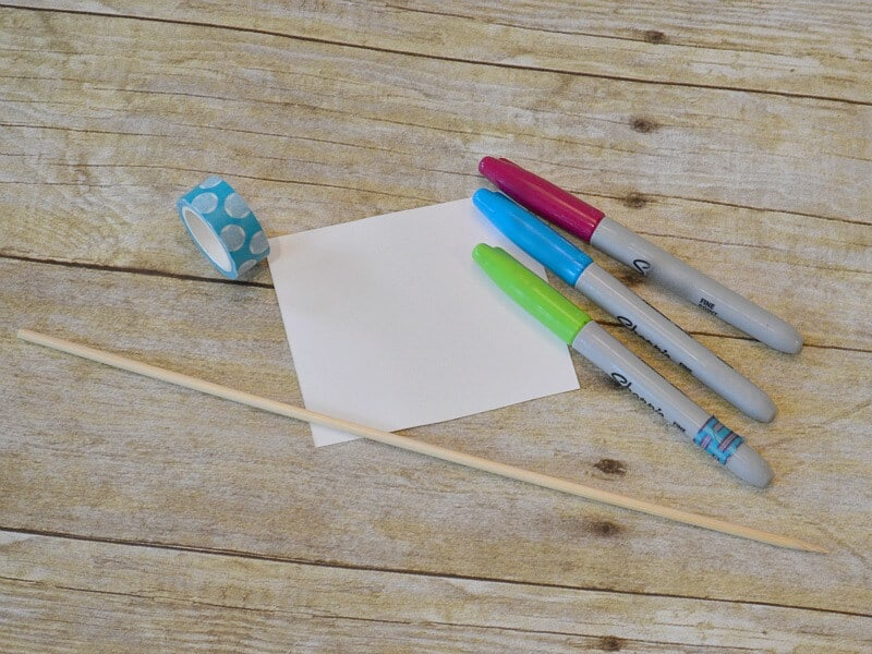 white square of paper, small dowel rod, and markers on wood table