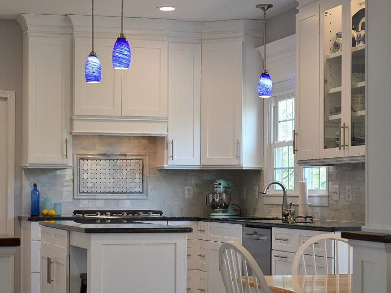 large modern kitchen with white cabinets and blue handing lights