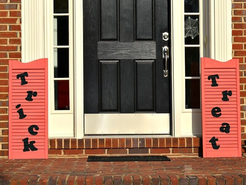 orange shutter signs on either side of black front door