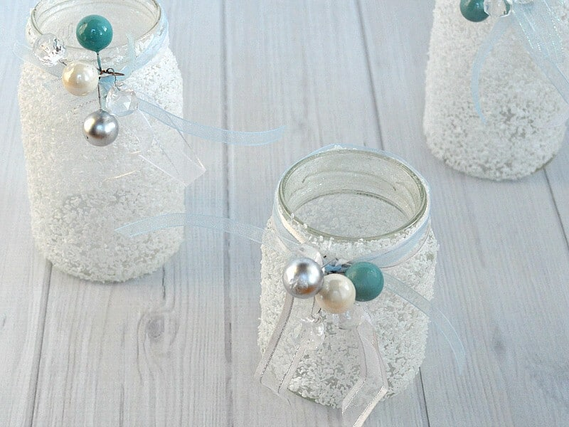 overhead view of 3 white frosty jars with ribbons and white, blue and silver beads