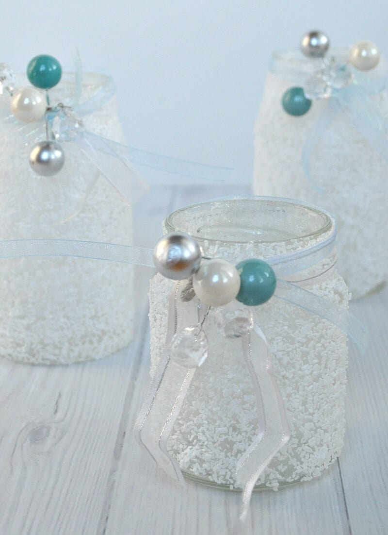 close up of 3 white frosty jars with ribbons and white, blue and silver beads on white wood table