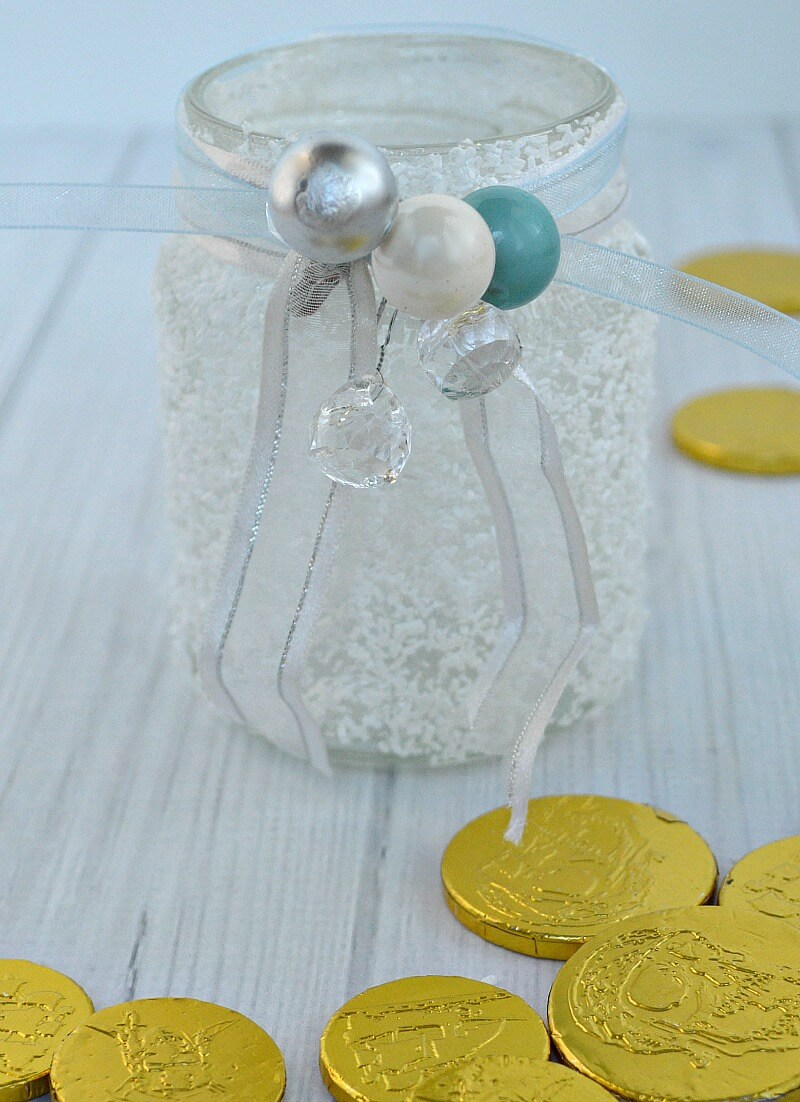 close up of white frosty jar with ribbons and white, blue and silver beads and gold foil coin candy