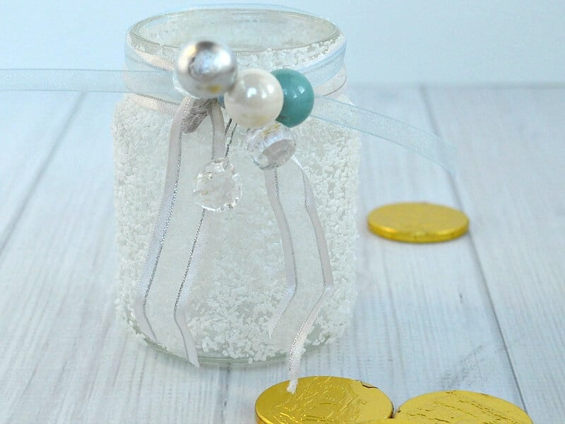 close up of 3 white frosty jar with ribbons and white, blue and silver beads and gold foil coins on table