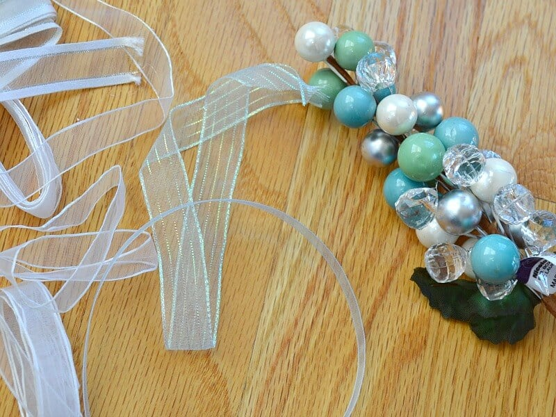 ribbon and blue, clear, silver and white beads on wood table