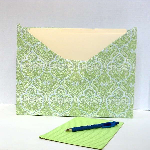 decorated file box with green pad of paper and pen