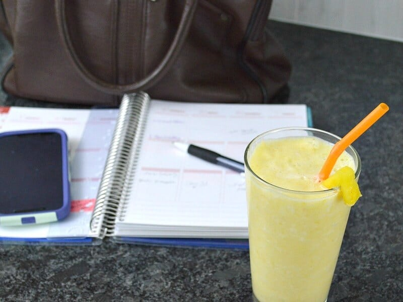 glass of frothy yellow drink with straw in front, behind phone, open planner, pen and brown purse on black counter